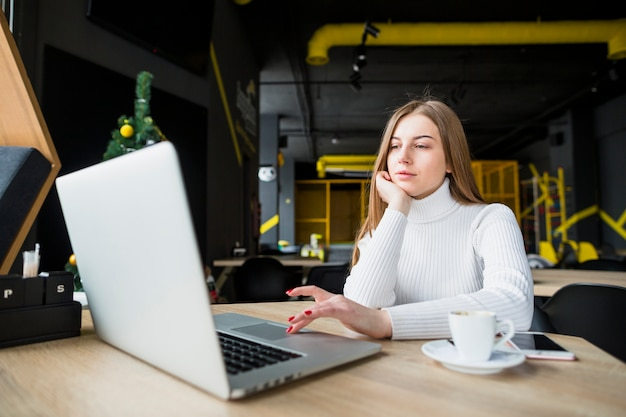 Porträt der modernen frau arbeitend mit laptop