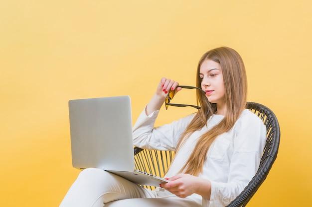 Porträt der modernen frau mit laptop auf stuhl
