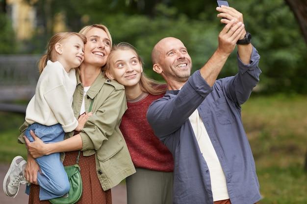 Porträt der modernen glücklichen familie mit zwei töchtern, die selfie-foto im freien beim genießen des spaziergangs im grünen park machen