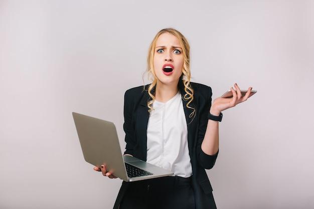Porträt der modernen hübschen blonden bürofrau im weißen hemd und in der schwarzen jacke. arbeiten mit laptop, telefon. erstaunt, verärgert, probleme, wahre gefühle ausdrücken, beschäftigt sein