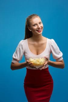 Porträt der modernen jungen blonden frau im rosa-roten kleid, helle make-upholding, gebratene kartoffel, chips und über blauer wand essend. ungesunde ernährung. junk-food-konzept