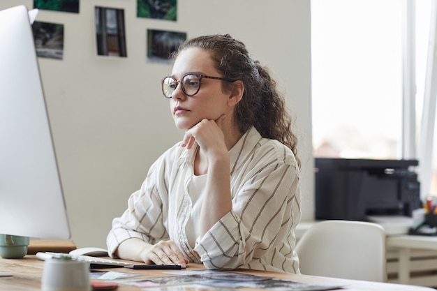 Porträt der modernen jungen frau, die brillen trägt, die computerbildschirm nachdenklich betrachten, während am schreibtisch im weißen büro, kopienraum arbeiten