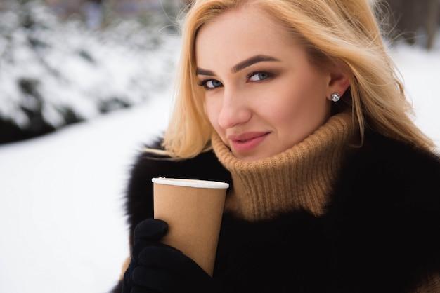 Porträt der modischen frau des europäischen stils, die kaffee im winterpark trinkt.
