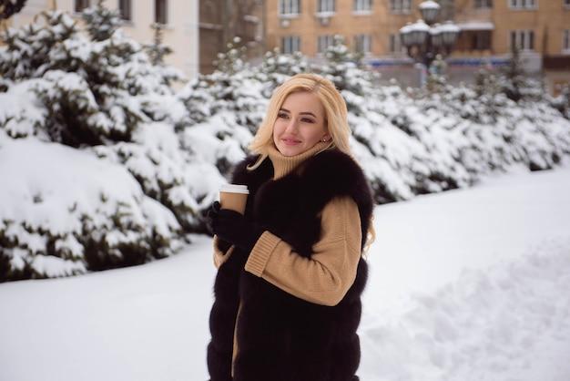 Porträt der modischen frau des europäischen stils, die kaffee im winterpark trinkt