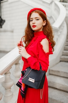 Porträt der modischen ingwerfrau in der roten baskenmütze und im eleganten kleid, das im freien aufwirft.
