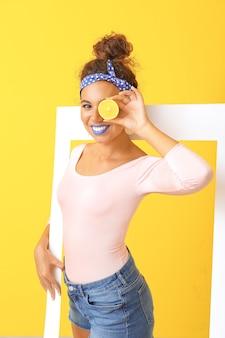 Porträt der modischen jungen afroamerikanischen frau mit rahmen und zitrone auf farbe
