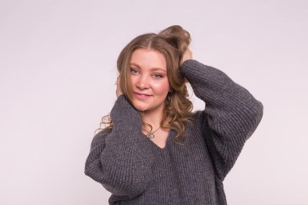 Porträt der modischen jungen blonden frau mit dem lockigen haar in der grauen strickjacke