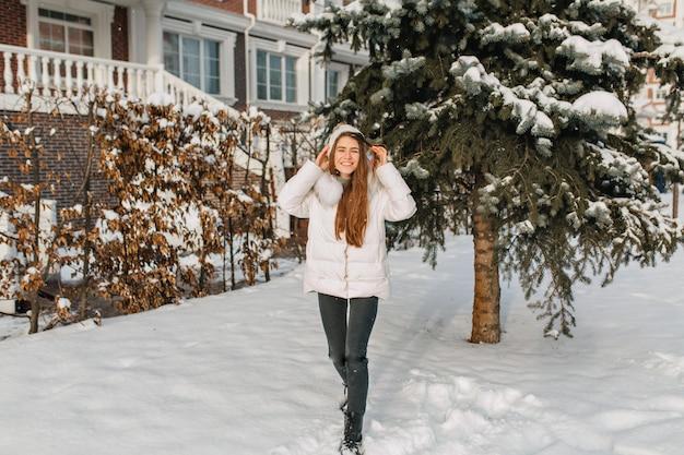 Porträt der modischen langhaarigen dame in voller länge, die neben haus nahe grünem schneebedecktem baum aufwirft. foto im freien der entzückenden kaukasischen frau in der jacke, die winterzeit im hof verbringt, der gutes wetter genießt.