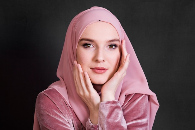 Porträt der moslemischen frau aufwerfend auf schwarzem hintergrund