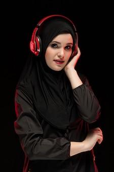Porträt der moslemischen frau schwarzes hijab tragend, das musik in den kopfhörern hört