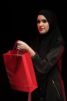 Porträt der moslemischen frau schwarzes hijab tragend, einkaufstasche als verkäufer anbietend