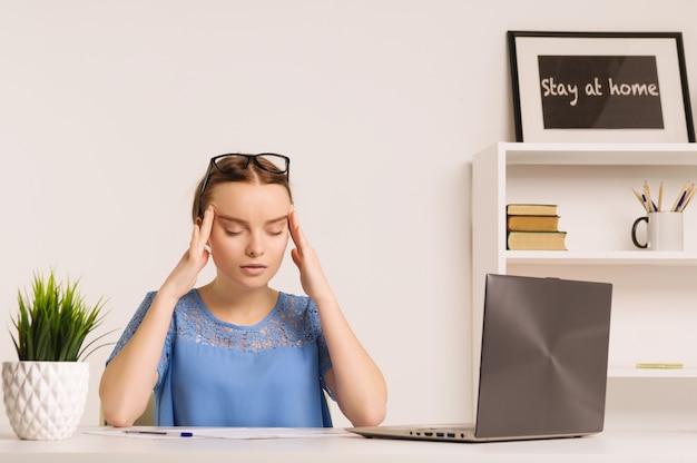 Porträt der müden geschäftsfrau, die kopfschmerzen am arbeitsplatz hat, nachdem sie für eine lange zeit mit computer gearbeitet hat - bild