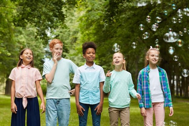 Porträt der multiethnischen gruppe von kindern, die im freien in reihe stehen, während mit blasen im park spielen