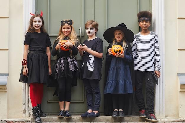 Porträt der multiethnischen gruppe von kindern in voller länge, die halloween-kostüme tragen, während süßes oder saures zusammen