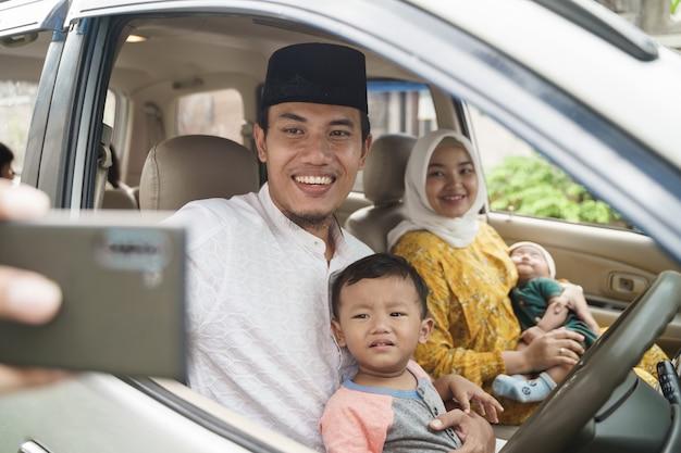 Porträt der muslimischen familie reisen mit dem auto und sprechen per videoanruf auf ihrem telefon