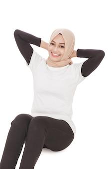 Porträt der muslimischen sportlichen frau, die beim lächeln aufsteht