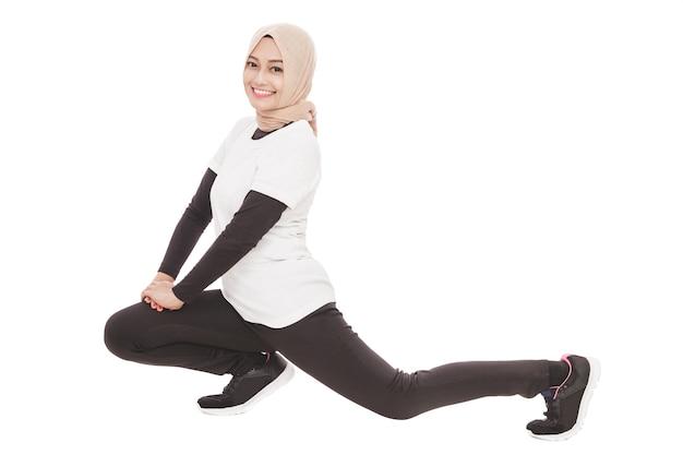 Porträt der muslimischen sportlichen frau, die beinstreckung tut