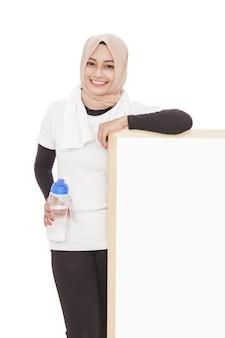 Porträt der muslimischen sportlichen frau, die eine flasche mineralwasser hält
