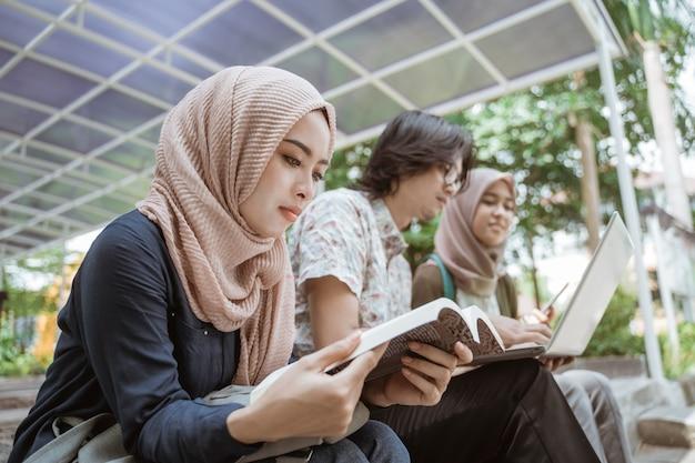 Porträt der muslimischen studentin, die ein buch liest