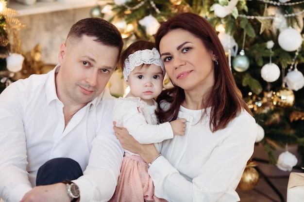 Porträt der mutter, des vaters und des reizenden kleinen mädchens, das vorne lächelnd am geschmückten weihnachtsbaum mit weihnachtskugeln sitzt