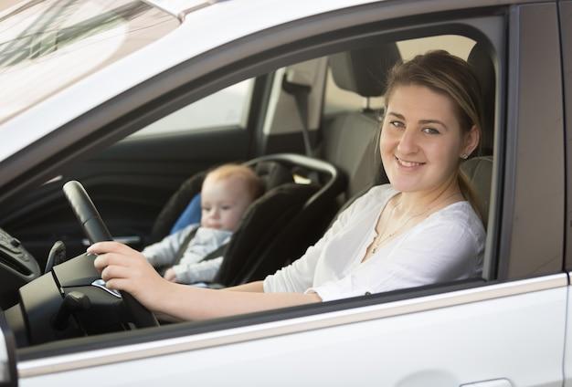 Porträt der mutter, die auto mit dem kleinen jungen fährt, der im sicherheitssitz sitzt