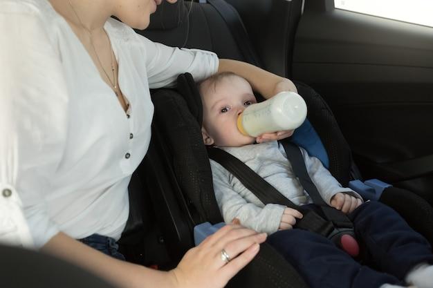 Porträt der mutter, die ihrem baby milch auf dem rücksitz des autos gibt