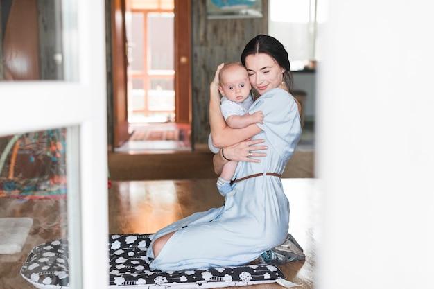 Porträt der mutter ihr baby zu hause liebend