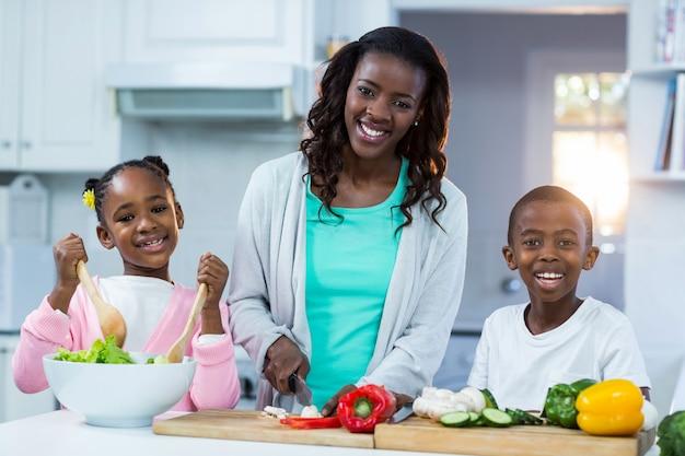 Porträt der mutter mit ihren kindern, die essen zubereiten