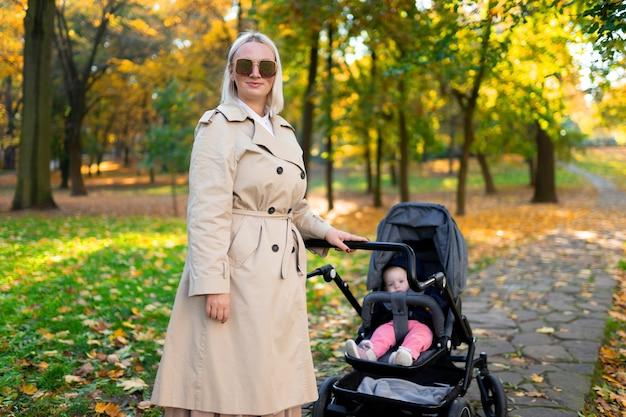Porträt der mutter mit kinderwagen im herbstpark