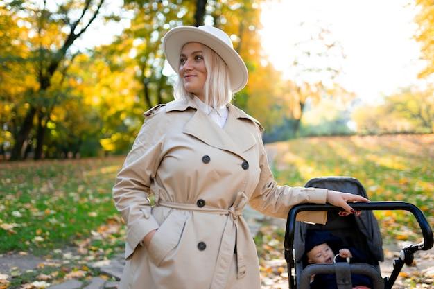 Porträt der mutter mit kinderwagen im park