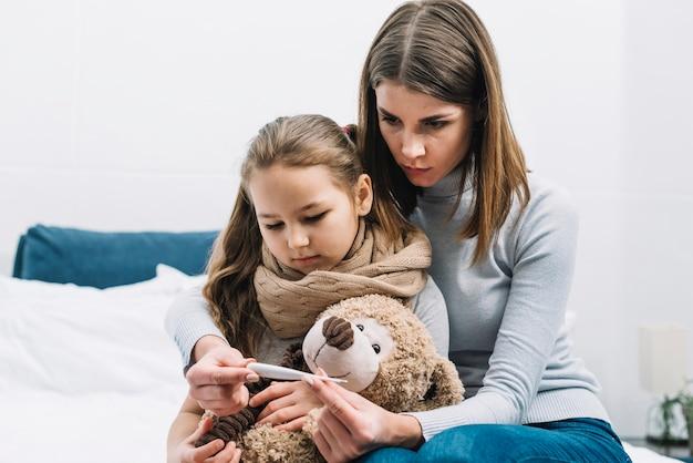 Porträt der mutter sitzend mit ihrer tochter, die den teddybären betrachtet thermometer hält