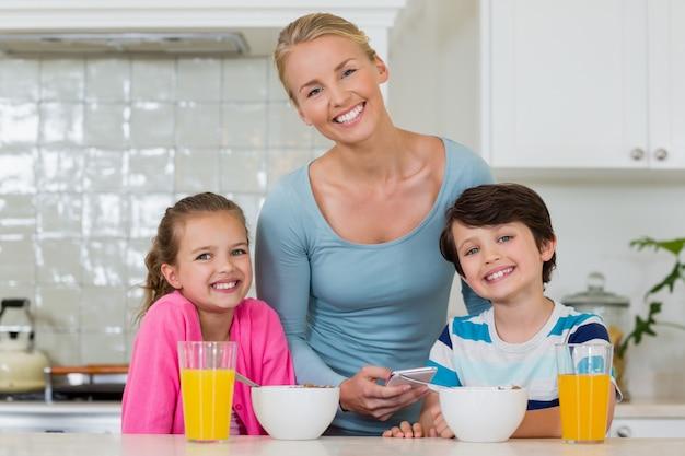 Porträt der mutter und der kinder, die in der küche stehen