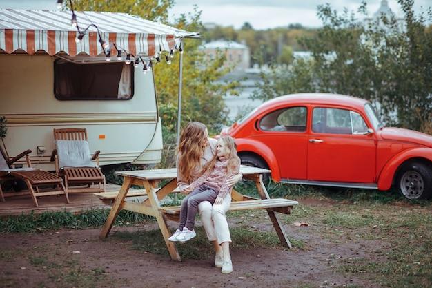 Porträt der mutter und der kleinen tochter, die in der landschaft auf reisemobilferien mit rotem retro- auto umarmen und sich entspannen