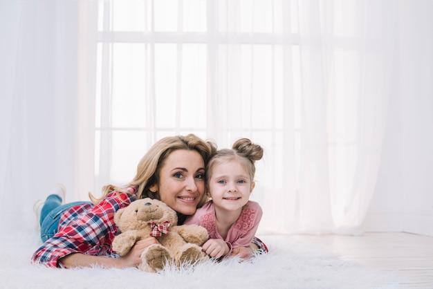 Porträt der mutter und der tochter, die auf dem pelzholding-teddybären liegt