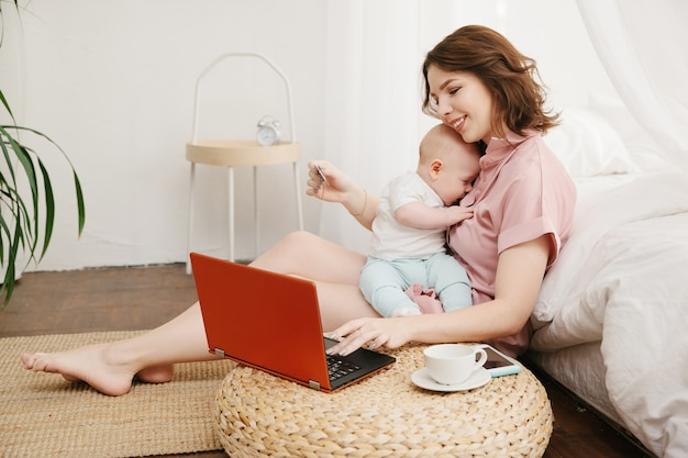 Porträt der mutter und des kleinen sohnes, die online-einkauf mit kreditkarte unter verwendung des laptops tun.