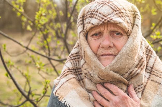 Porträt der nachdenklichen alten großmutter, die sich auf zuckerrohr stützt