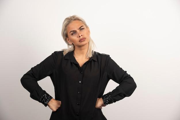 Porträt der nachdenklichen frau im schwarzen hemd, das auf weißem hintergrund aufwirft. hochwertiges foto