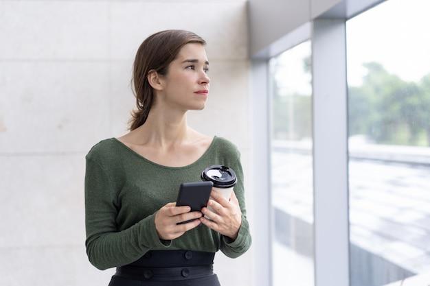 Porträt der nachdenklichen jungen frau, die handy und kaffee hält