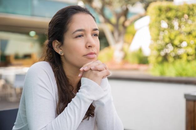 Porträt der nachdenklichen oder traurigen jungen frau, die am straßencafé sitzt