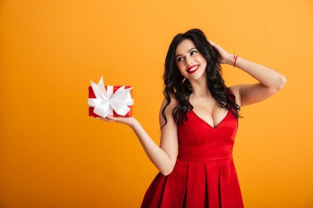 Porträt der netten alleinstehenden frau 20s im roten kleid, die ihre geschenkbox mit geschenkverpackung genießt, lokalisiert über gelber wand