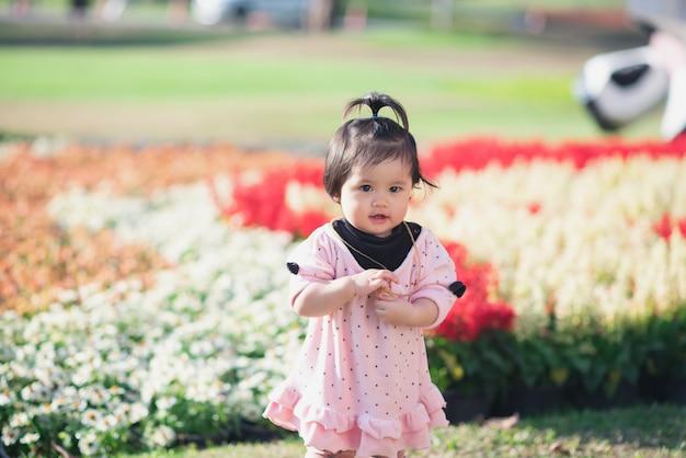 Porträt der netten babyreise am blumengarten