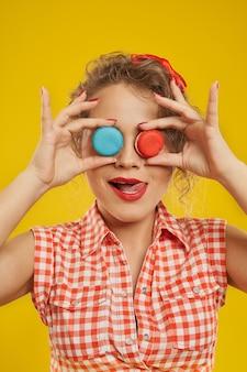 Porträt der netten frau, die ihre augen mit macarons bedeckt