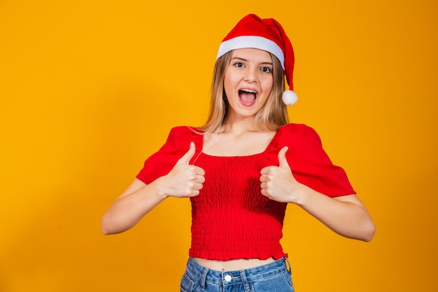 Porträt der netten frau, die sich daumen zeigt und trägt weihnachtsmann-hut.