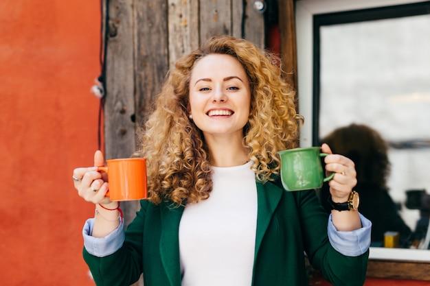 Porträt der netten frau mit der reinen haut, die stilvolle frisur hat, kleidete in der grünen jacke an.