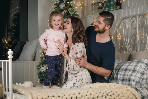 Porträt der netten glücklichen familie in den pyjamas auf weihnachten auf bett