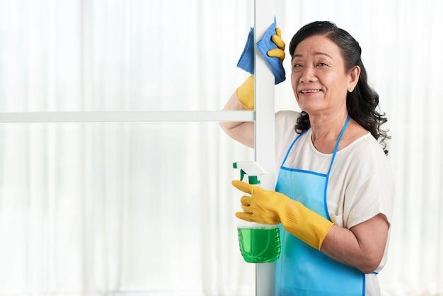 Porträt der netten haushälterin aufwerfend an der glastrennwand mit reinigungsmittelspray