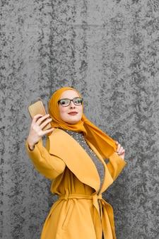 Porträt der netten jungen frau, die ein selfie nimmt