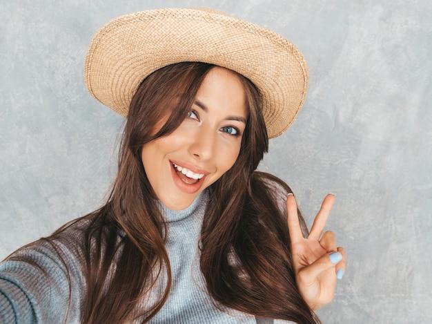 Porträt der netten jungen frau, die foto selfie macht und moderne kleidung und hut trägt. . zeigt friedenszeichen