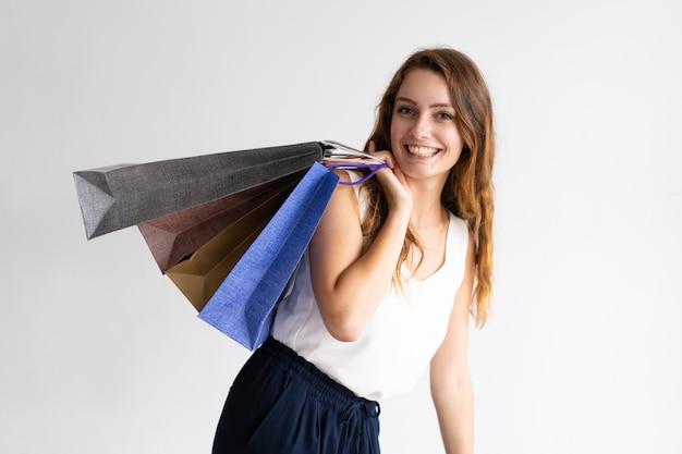 Porträt der netten jungen kaukasischen frau, die einkaufstaschen hält