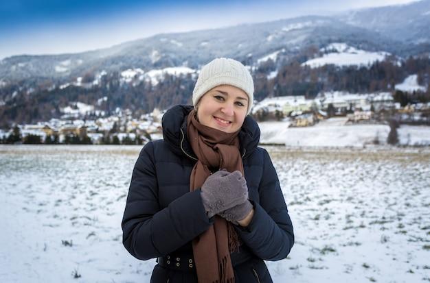 Porträt der netten lächelnden frau, die gegen hohe schneebedeckte berge aufwirft